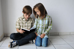 Siblings. Big brother is reading for his little sister Stock Photo