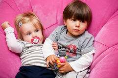 Siblings. Two young children (siblings) sitting on pink puffy chair Royalty Free Stock Images