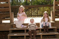 Siblings. Two sisters and their brother sitting on stairs Royalty Free Stock Photo