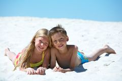 Siblings. Photo of happy siblings lying on sand on summer vacation Royalty Free Stock Photos