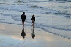 Siblings. Brother & sister paddling on the beach royalty free stock photo