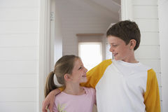 Siblings With Arms Around Looking At Each Other Royalty Free Stock Image