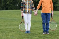 Siblings with badminton racquets holding hands and standing on green grass. Cropped shot of siblings with badminton racquets holding hands and standing on green stock photos