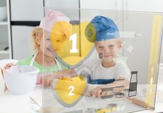 Siblings baking with hologram interface Royalty Free Stock Photo