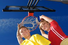 Siblings by the basket hoop. Playing basketball Royalty Free Stock Image
