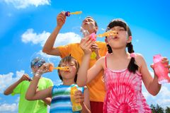 Siblings blowing bubbles Stock Photo
