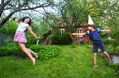 Siblings boy and girl play harry potter game. With magic stick royalty free stock photos