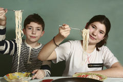 Siblings boy and girl with spaghetti Stock Image