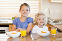Siblings with breakfast behind the kitchen counter Royalty Free Stock Image