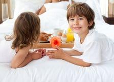 Siblings bringing breakfast to their parents. Close-up of siblings bringing breakfast to their parents in the bedroom stock image