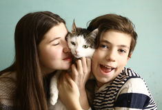 Siblings brother and sister with cat cuddle and smile Stock Images