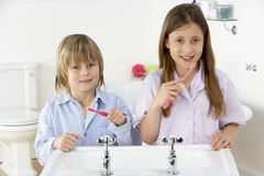 Siblings Brushing Teeth Together at Sink Stock Images