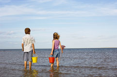 Siblings With Buckets And Fishnet Enjoying Sea View Royalty Free Stock Photography