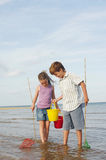 Siblings With Buckets And Fishnets In Water Royalty Free Stock Images