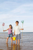 Siblings With Buckets And Fishnets In Water Stock Photo