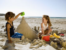 Siblings building sandcastles on the beach. Royalty Free Stock Photo