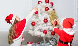 Siblings busy decorating. Boy and girl decorating tree. Cherished holiday activity. Kids in santa hats decorating royalty free stock photo