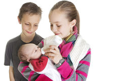 Siblings Caring for their new Baby Brother. Two older siblings feeding and caring for their new baby brother Royalty Free Stock Photos