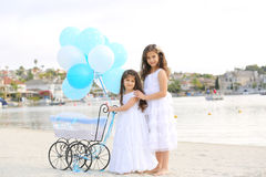 Siblings with carriage. Two sisters standing by a baby carriage with dozen of white and blue balloons Stock Photography