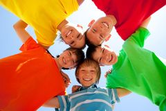 Siblings in a circle. Five smiling siblings arm in arm in a circle, with their heads together in the middle looking downward toward the viewer, with a blue sky Stock Photography