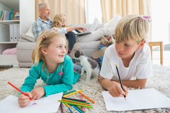 Siblings colouring and drawing on the floor Royalty Free Stock Photography