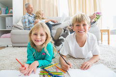 Siblings colouring and drawing on the floor Stock Photo