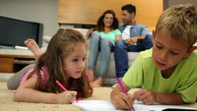 Siblings colouring on the floor while their parents are sitting on sofa