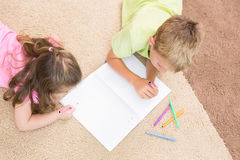 Siblings colouring on the rug Stock Image