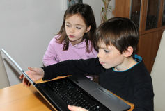 Siblings with computer. Siblings with laptop computer surfing in internet Stock Images