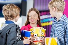 Siblings Conversing While Holding Snacks At Cinema Stock Photo