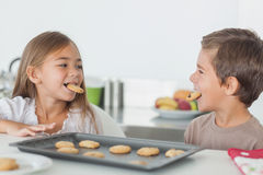 Siblings with cookies in their mouth Stock Photo