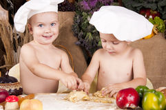 Siblings cooking in chef\'s hats Stock Photo