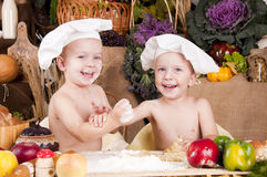 Siblings cooking in chef\'s hats. And smiling Royalty Free Stock Images