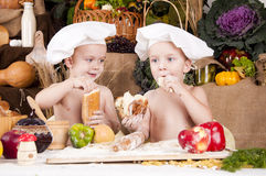 Siblings cooking in chef\'s hats Stock Photos