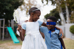 Siblings in costumes standing at park Royalty Free Stock Photography