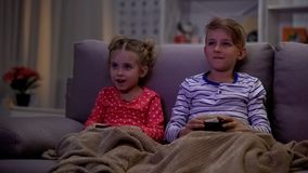 Siblings covered with plaid enjoying video game, playing at night, using console. Stock photo royalty free stock photography