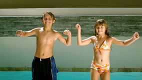 Siblings dancing together in front of the swimming pool stock footage