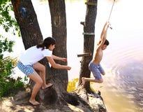 siblings de broer en de zuster onderhouden zich met waterschommeling op vakantie Stock Fotografie