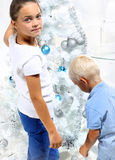 Siblings decorates the Christmas tree Stock Photos