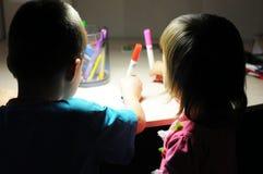 Siblings die avondhuis schilderen bij lamp lichte, hoge ISO Stock Afbeeldingen