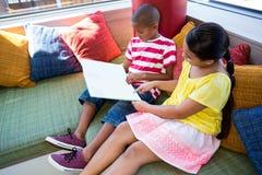 Siblings die boek thuis lezen Stock Foto