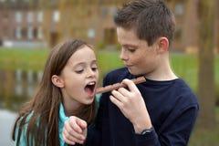 Siblings die chocolade eten Stock Afbeeldingen