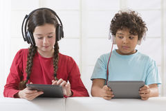 Siblings die digitale tablet gebruiken terwijl het luisteren royalty-vrije stock afbeeldingen