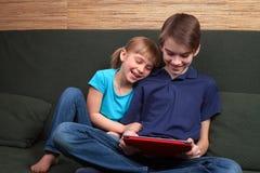 Siblings die een tabletcomputer met behulp van Stock Foto's