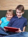 Siblings die een tabletcomputer met behulp van Stock Fotografie