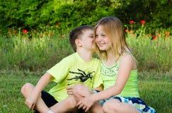 Siblings die geheimen delen Stock Foto's