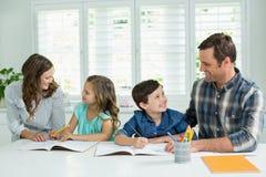 Siblings die hulp met thuiswerk van ouders krijgen stock foto