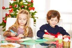 Siblings die kaarten trekken bij Kerstmis Stock Foto's