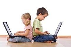 Siblings die laptops met behulp van Royalty-vrije Stock Foto