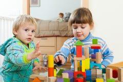 Siblings die met houten speelgoed spelen Royalty-vrije Stock Afbeeldingen